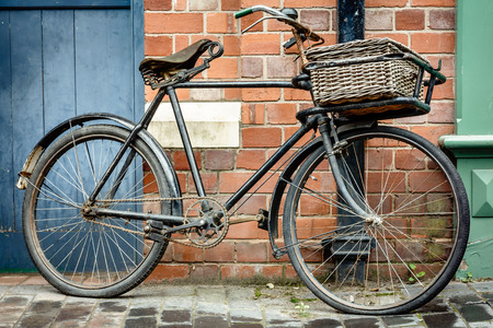 cicla: Ciclo de retro viejo con cesta apoyado contra una pared de ladrillo Foto de archivo