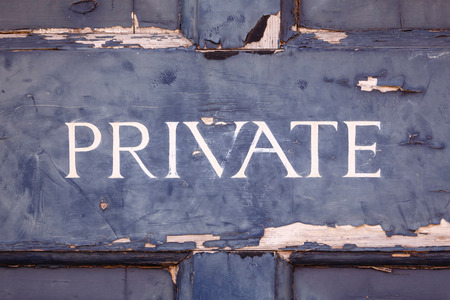 Closeup of a private sign on an old blue door with peeling paint photo