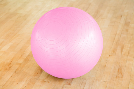floorboards: Closeup of a pink swiss ball in a gym