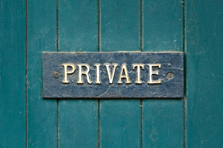panelled: Closeup of a private sign on an old wooden door painted green Stock Photo