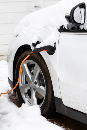 plugged in': Electric car plugged in to an outlet recharging outdoors in winter snow