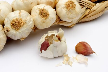 whitespace: Detail of a garlic bulbs with cloves in the foreground.