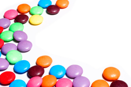 whitespace: Colorful candy arranged in a pattern on a white background with copy space