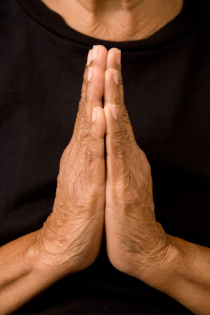 worshiper: An old asian woman holds her hands in prayer