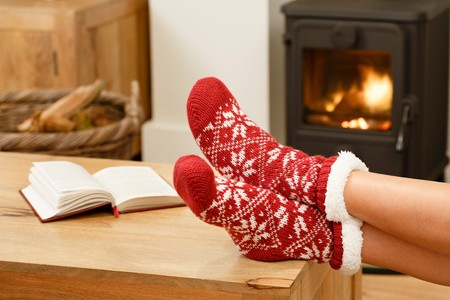 christmas fireplace: Woman in Christmas socks relaxing next to a wood burning stove