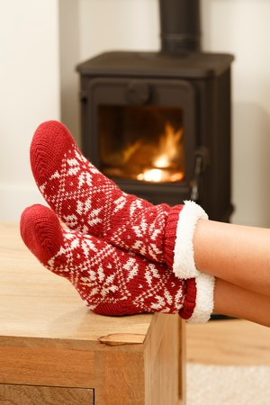 burn out: Woman warming feet in front of a cosy fire at Christmas time