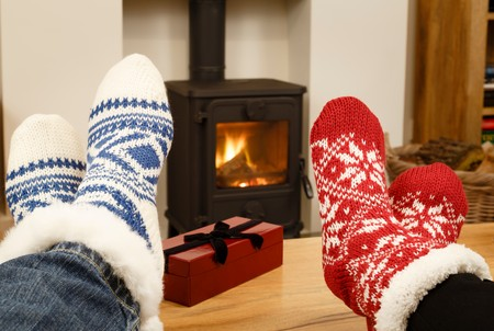 woodburner: Couple relaxing in Christmas socks in front of cozy fire