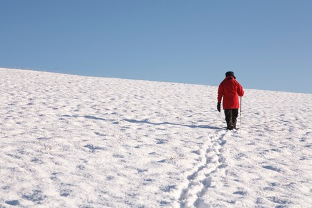 snowscene: Woman walking alone up a snow covered hill in winter Stock Photo