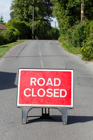 Road sign on a street showing a road closure Imagens