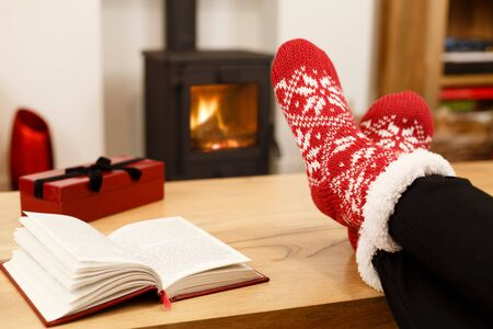 woodburner: Woman relaxing at home in front of a cozy fire at Christmas