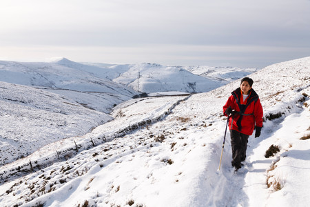 Indian woman hiking in winter snow, Peak District, UK
