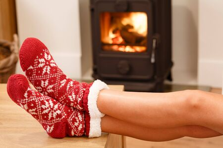 woodburning: Womans feet in red Christmas socks by cozy wood burner