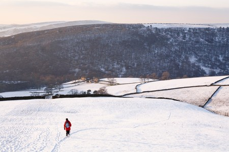 snowscene: Woman walking in snow covered countryside, Peak District, UK Stock Photo