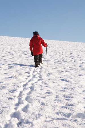 snowscene: Woman hiking alone up a snow covered hill in winter Stock Photo
