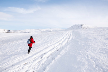 snowscape: Woman hiking in snow, Peak District, Derbyshire, UK Stock Photo