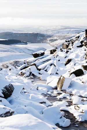 Snow covered countryside in winter with Kinder Reservoir viewed from Kinder Scout, Peak District, UK