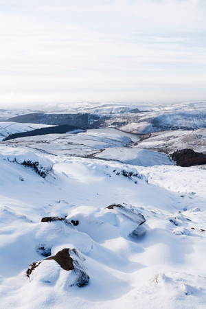 Snow covered countryside in winter with Kinder Reservoir viewed from Kinder Scout, Derbyshire, UK