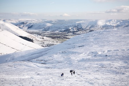 snowscene: PEAK DISTRICT, UK - CIRCA 2012: A group of people hiking on Kinder Scout in winter with Edale valley in the distance. Peak District, UK Editorial