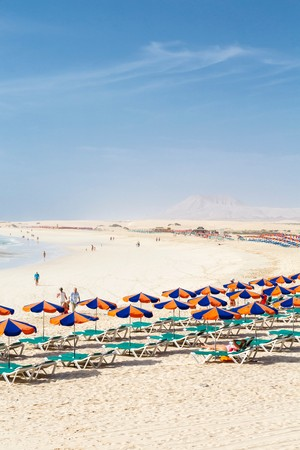 FUERTEVENTURA, SPAIN - CIRCA 2013: Row of sunbeds and parasols on sandy beach Bajo Negro, Fuerteventura, Canary Islands