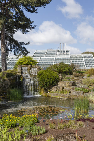 London, UK - April 18, 2014. Rock garden and Princess of Wales Conservatory in Kew Botanic Gardens. The gardens were founded in 1840 and are of international significance for botanical research and education. Editorial