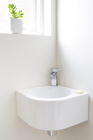 Modern corner wash basin in a minimalist cloakroom Stock Photo
