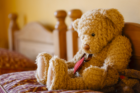 Sad faced teddy bear sitting alone on a bed. Depicts loneliness and depression Stock Photo