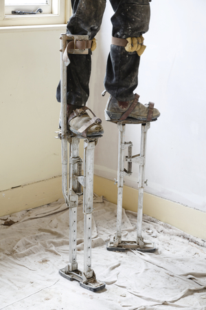 Plasterer on stilts plastering a high ceiling Banque d'images