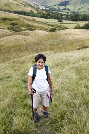 An Indian Asian woman hikes in British countryside