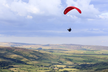 Peak District, UK - August 08, 2007. A paraglider flies over Edale Valley in the Peak District, Derbyshire. The pilots gain lift from the strong updraft that occurs on windward hill slopes.