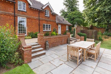 Großes historisches viktorianisches Haus mit englischem Garten und Terrasse mit Holzmöbeln. Buckinghamshire, Großbritannien