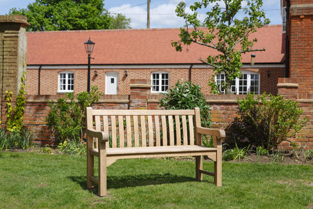 Teak hardwood bench on a lawn in an English garden with historic Victorian home in the background Stockfoto