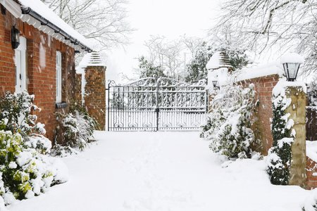 Entrance to Victorian house with cast iron gates with driveway covered in snow in winter Stockfoto