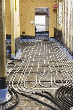 Underfloor heating water pipes installation to subfloor of a house under construction Imagens
