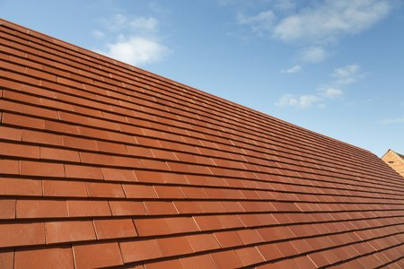 New traditional plain clay tiles on a house roof against a blue sky with copy space