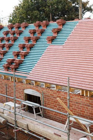 A roof on a building site in the process of being tiled with plain clay tiles