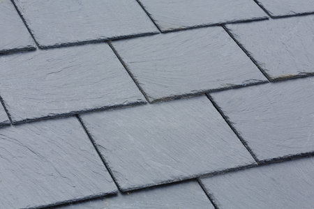 Closeup of traditional grey slate roof tiles on a pitched roof Stock Photo