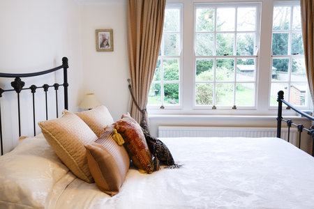 Bedroom of a period British house with sash windows and traditional interior design