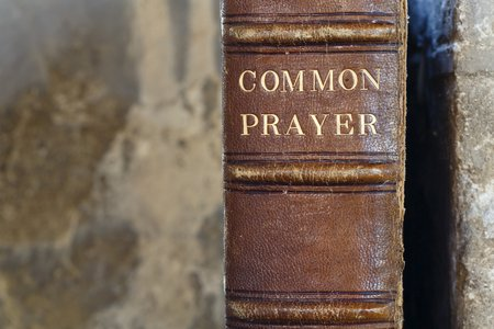 Detail of an old leather-bound christian prayer book with a stone background and copy space