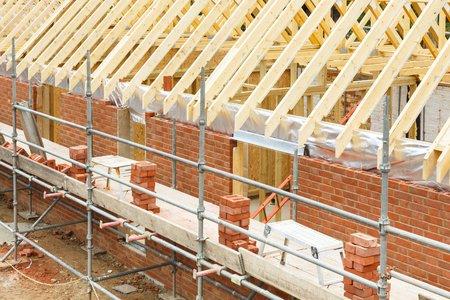 Chantier de construction au Royaume-Uni avec une maison construite en briques et en bois, avec des briques, des fermes de toit et des échafaudages