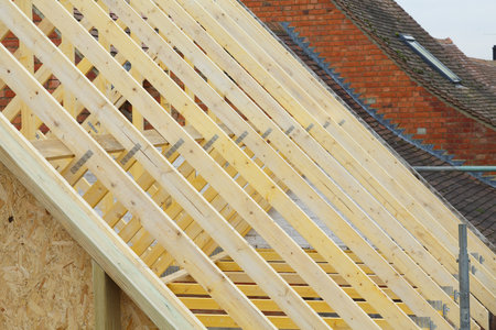 Detail of new timber roof trusses on a new roof being installed to a period house restoration in England Stock Photo