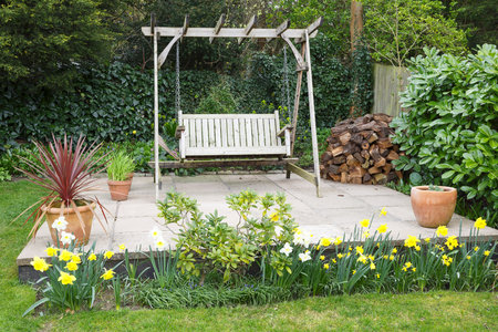 Garden patio in spring with daffodils and a wooden swing bench