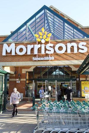 London, UK - February 25, 2019. Shoppers outside the front of a Morrisons supermarket in Hatch End, London. WM Morrison is the UK's fourth largest chain of supermarkets Editorial