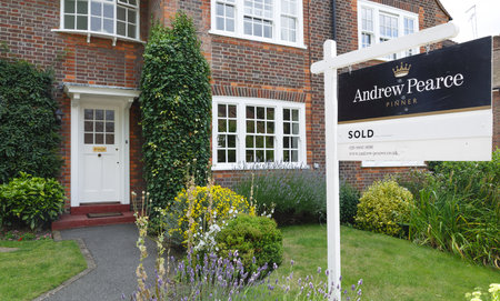 London, UK - July 15, 2014. A London estate agent sold sign is displayed outside a suburban semi-detached house in Pinner, northwest London. Sajtókép