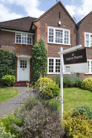 London, UK - July 15, 2014. A London estate agent sold sign is displayed outside a suburban semi-detached house in Pinner, northwest London. Editorial
