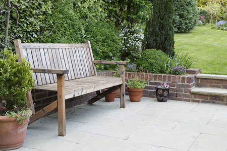 British back garden with a paved patio and traditional wooden bench 版權商用圖片