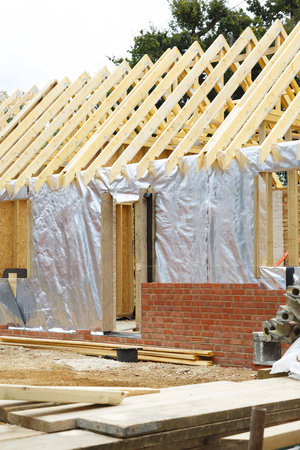 New build house construction using modern timber frame and insulation with a brick exterior wall