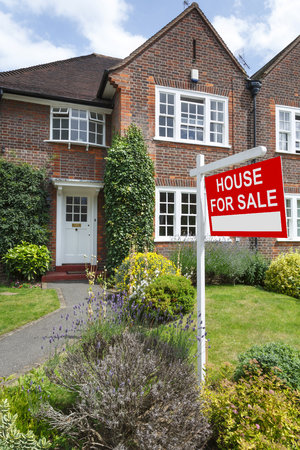 House for sale sign outside a typical UK semi-detached house in London