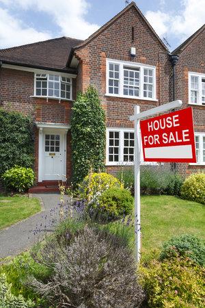 Znak domu na sprzedaż przed typowym brytyjskim bliźniakiem w Londynie