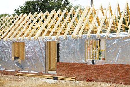 Timber frame house extension or annexe under construction with modern foil insulation and exterior brick wall