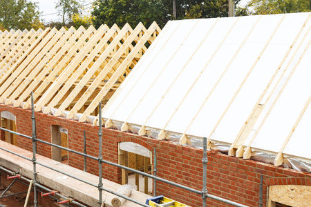 Installation of solid insulation sheets into roof trusses on a house build
